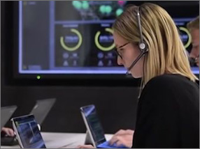 A woman infront of a laptop with a headset