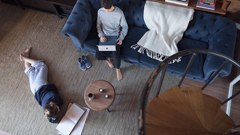 Two students study in a room together; one is lying on the floor and one is sitting on a couch with a Surface Pro in his lap.