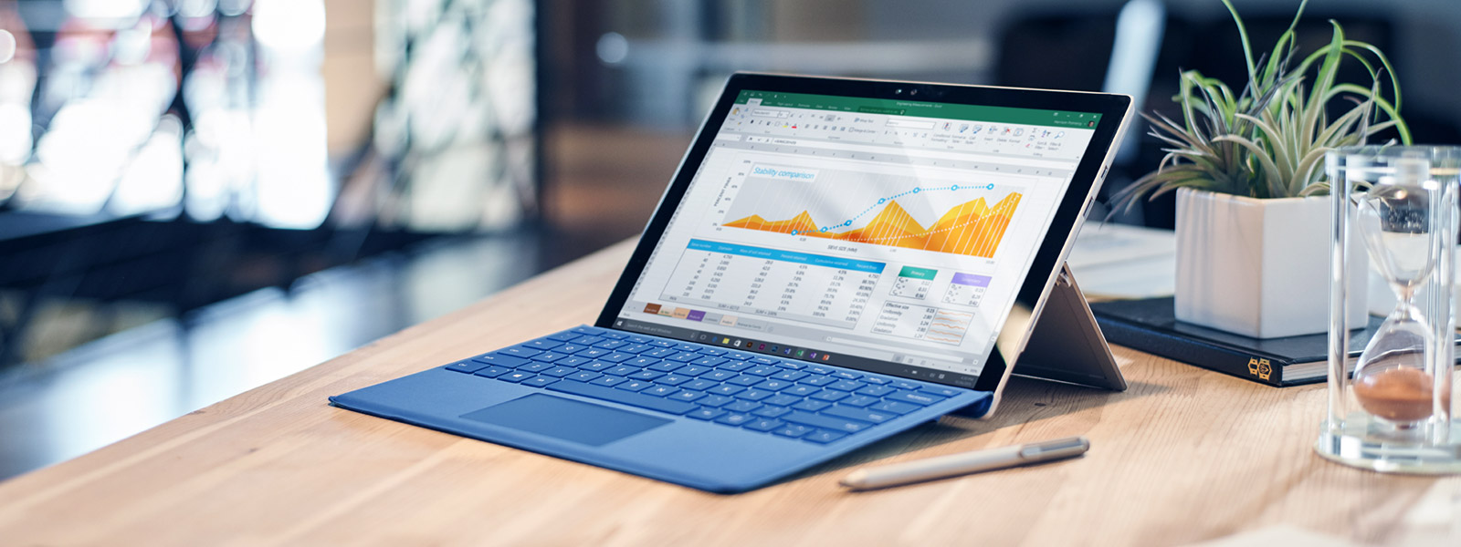 Surface Pro 4 with Excel spreadsheet on screen, sitting on a wooden table.