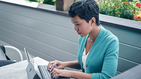 Woman types on Surface Pro 4 in an outdoor setting.
