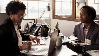 Two people at a desk working and one has a laptop open