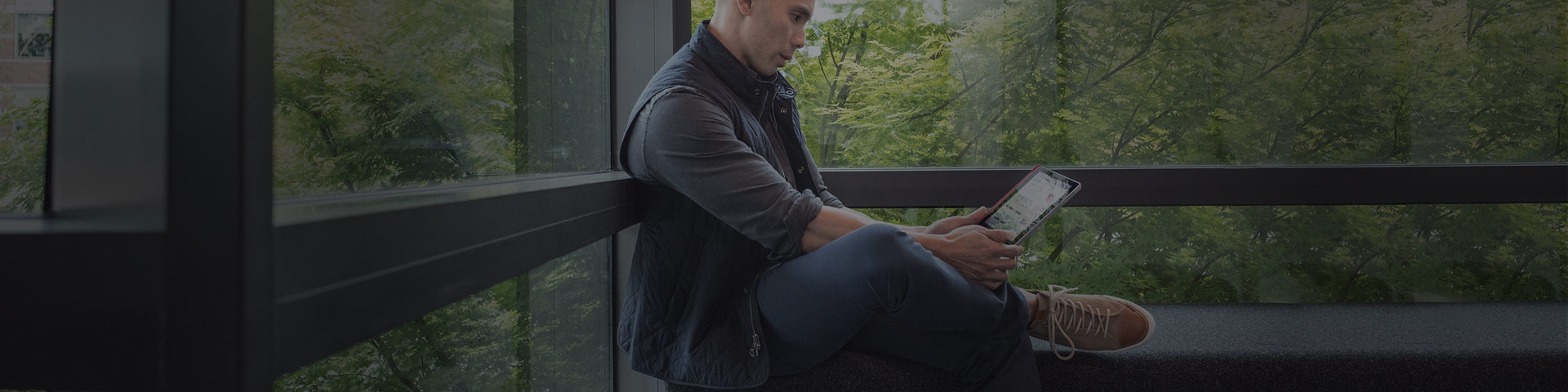 A man sits on a bench, looks at a device in his hands