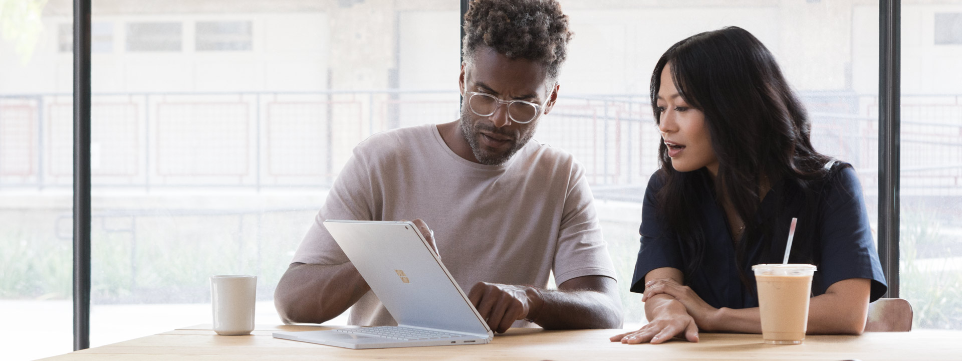 Man and woman using  a Surface Book 2 as a tablet with a keyboard folded under as a support stand.