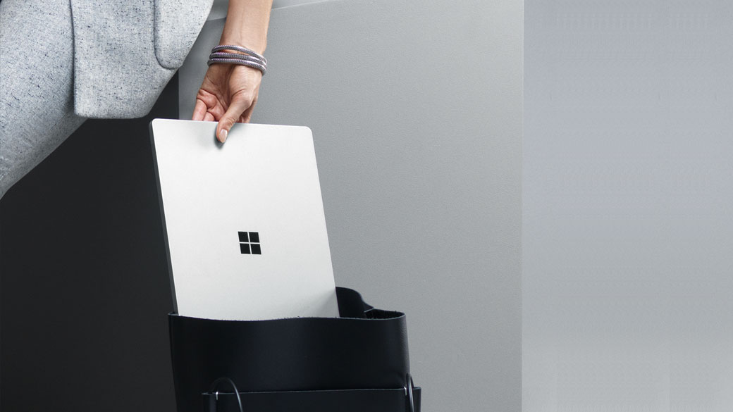 Woman taking Platinum Surface Laptop out of a bag.