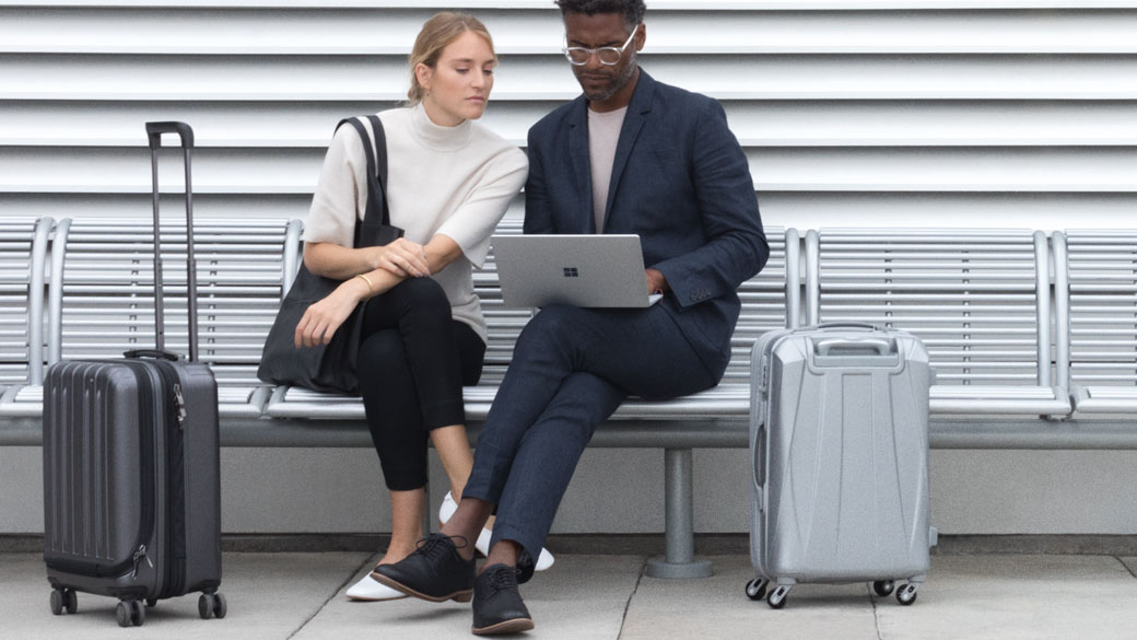 Woman and Man sitting on bench working on Platinum Surface Laptop with 2 suitcases.