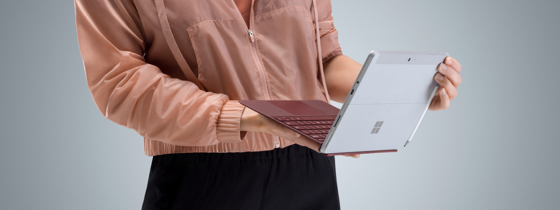 Girl in pink jacket holding Surface Go