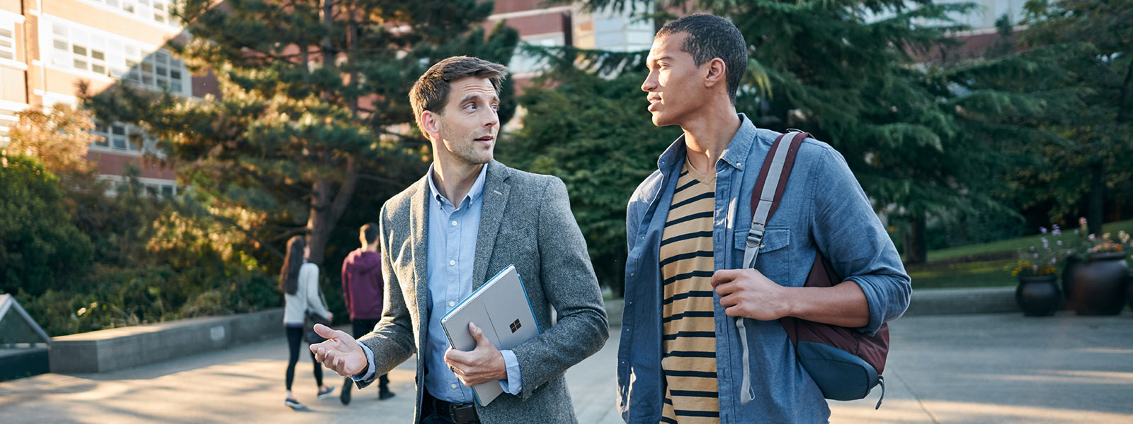 Two men walking across campus, one holding Surface Pro 4.