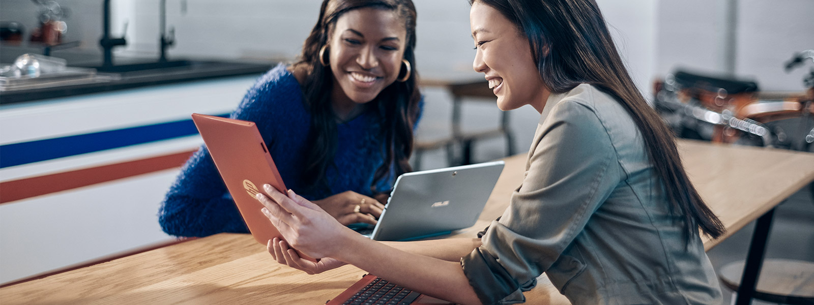 Two women seated at a table, looking at a tablet screen being help up between them by the other woman