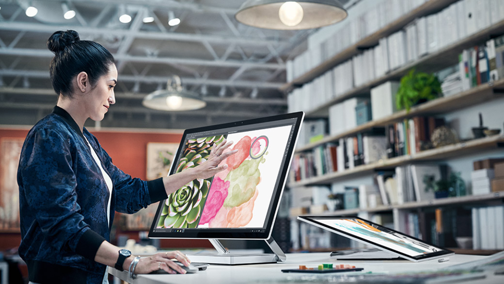 Woman touches the screen of a Surface Studio with her left hand, and has her right hand on a Surface Mouse. Adobe Illustrator CC is shown on the Surface Studio screen.