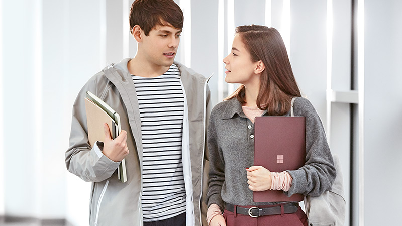 A male student holding a notebook and a female student holding a Burgundy Surface Laptop walk together in a hallway.