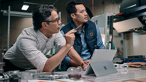 Two men working on Surface Pro 4 at an inspection site.