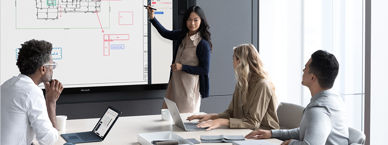 Co-workers sit at a conference table, while one woman uses Surface Pen on a Surface Hub, and a man uses a Cobalt Surface Laptop in laptop mode, and another woman uses Surface Book 2 in laptop mode.