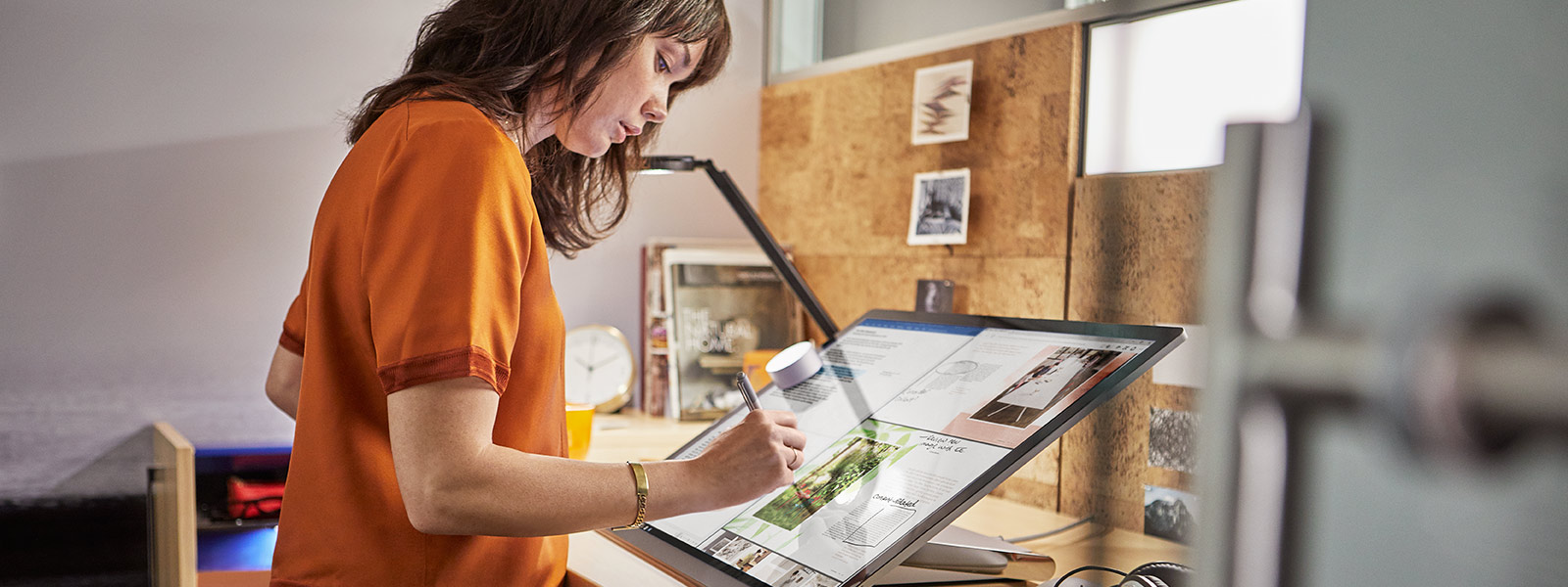 Woman uses pen on Surface Studio.