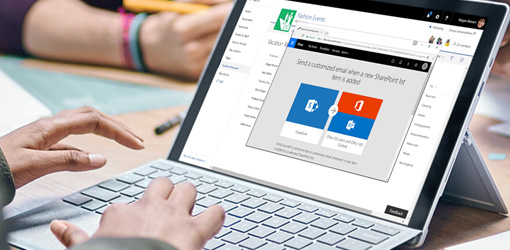 Hands typing on the keyboard of a laptop running Flow and SharePoint