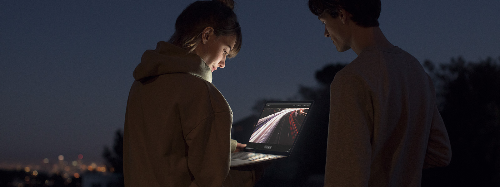 Two people using Surface in the dark.