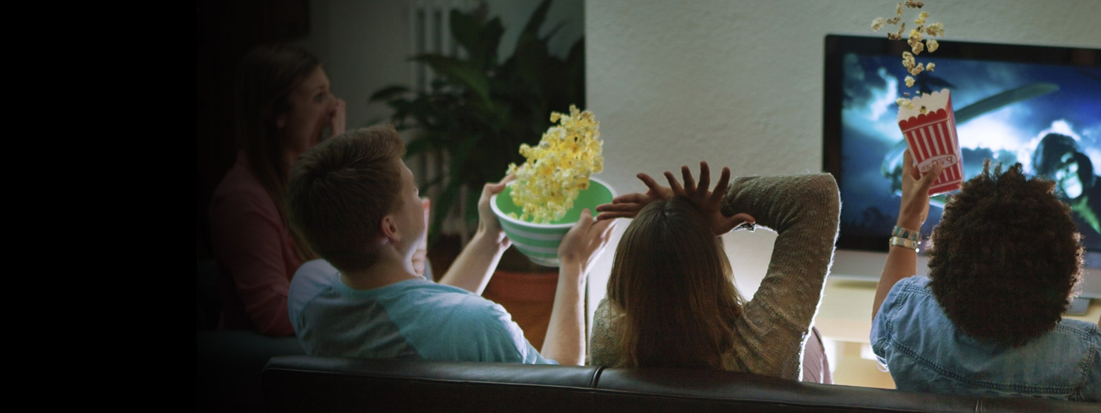 People sitting on a sofa watching a film