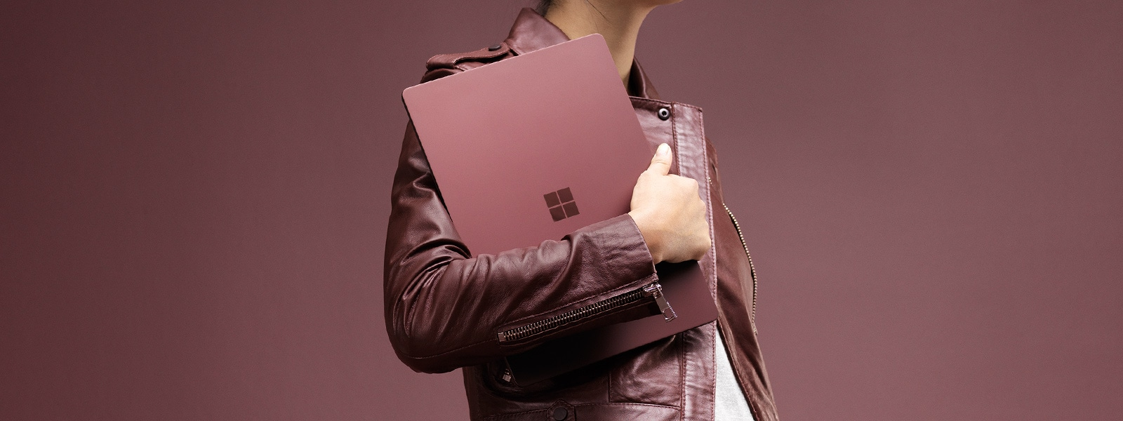 Fashionable woman holding the Burgundy Surface Laptop close to her chest