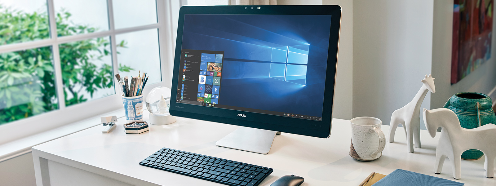 An ASUS desktop on a desk with a wireless mouse and a keyboard besides it