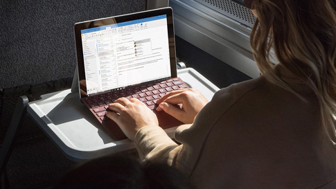 A woman works on Surface Go with Surface Go Signature Type Cover on a train
