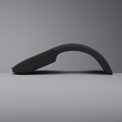 A Surface Arc mouse sits on a flat table