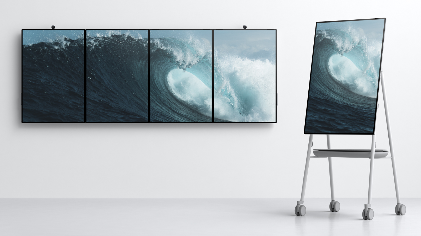 Four Surface Hub 2X smart boards tiled together on wall in portrait orientation, and one Surface Hub 2X rotated to a portrait orientation on a stand designed by Steelcase