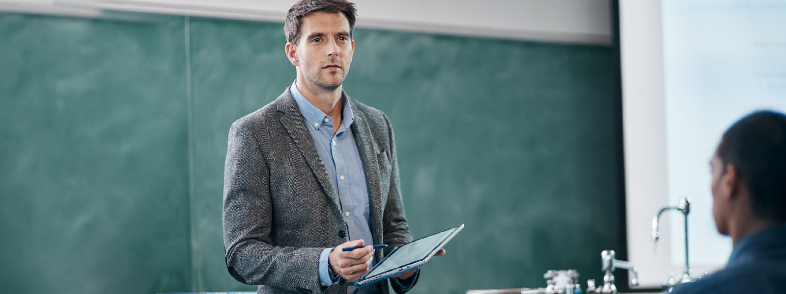 Teacher uses Surface Pro 4 in tablet mode as he lectures from front of classroom.