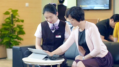 Two women use Surface pro 4 in a bank