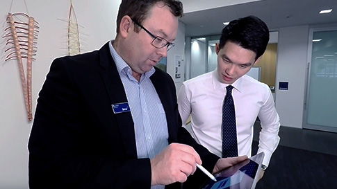 Man uses pen on touchscreen of Surface Pro 4 with another man looking over shoulder.