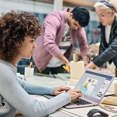 Woman working on 3D image on her laptop at table with designer colleagues