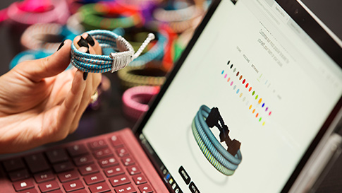 Woman holding a bracelet working on a Surface Pro.