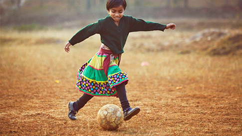 A child plays soccer in a field.
