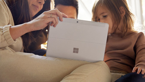 Family members gathered around a Surface computer