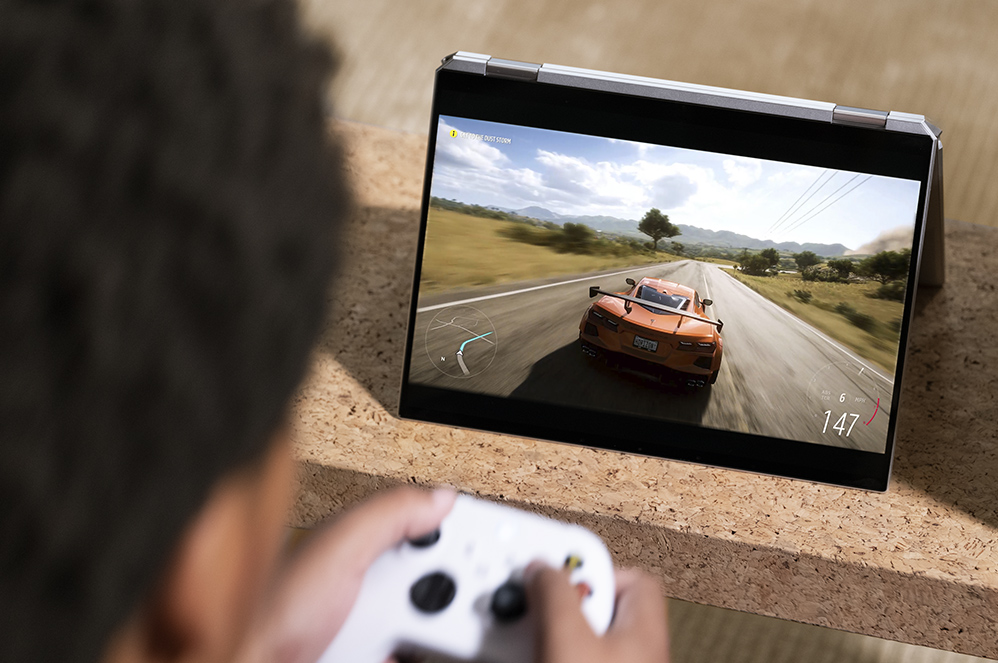 A man plays a racing video game on his PC with the XBOX controller