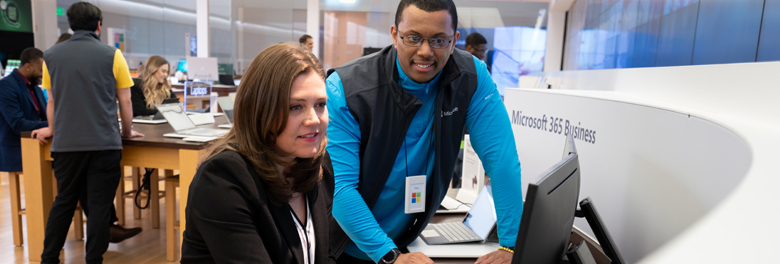 Male employee helping female customer with a PC at a Microsoft store.