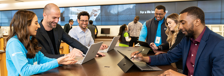 Male and female employee working with group of people on Surface devices.