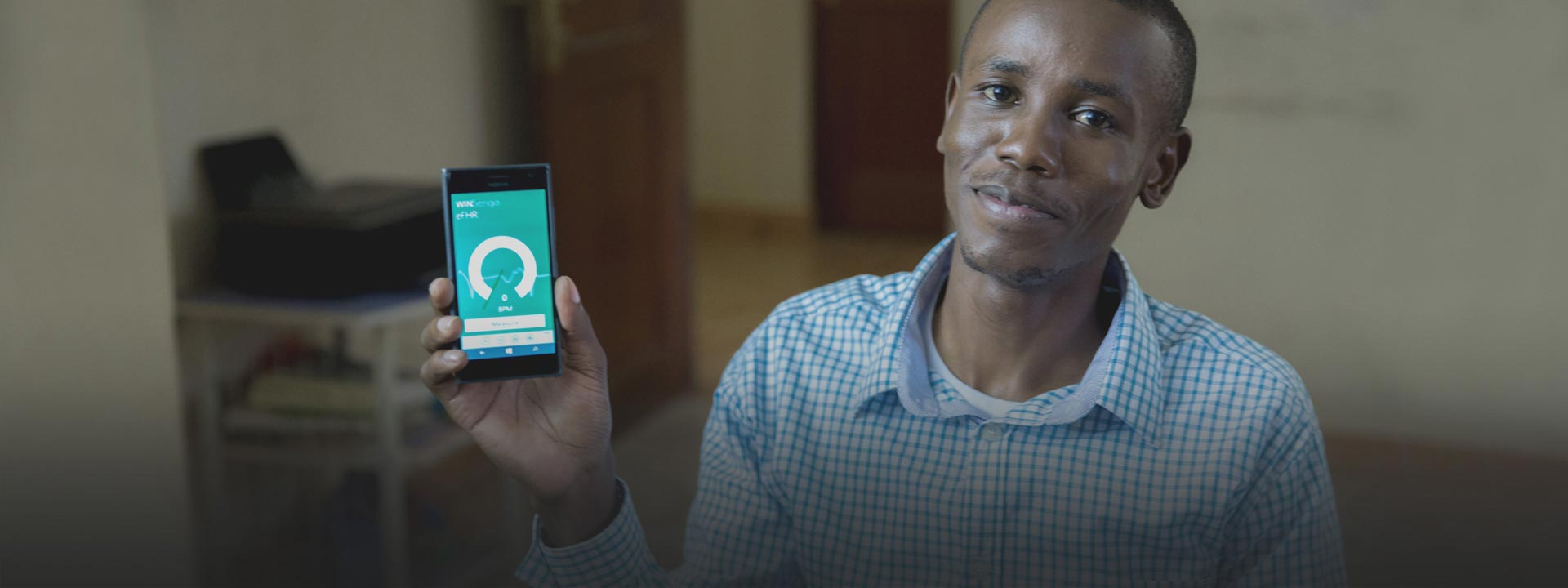 Smiling man holding a phone with the screen showing the WinSenga app