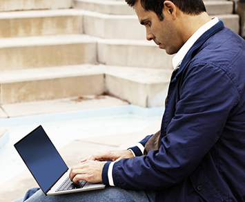 Photograph of a man sitting outside and working on a laptop computer.