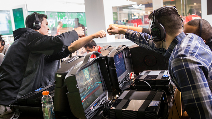 Teenagers fist pump while playing Gears of War at the Microsoft Store.