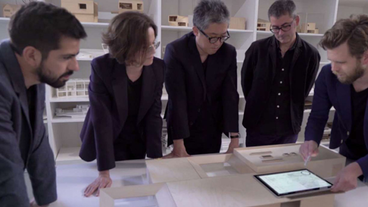 Five people surrounding table with Surface Pro 4on table