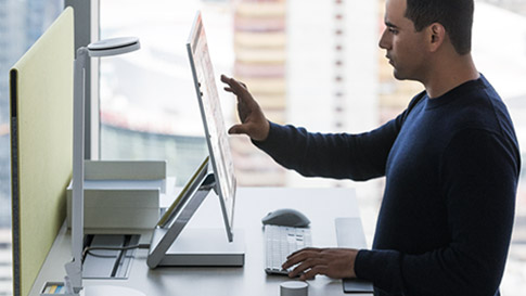 Man working in Surface Studio using touch screen.