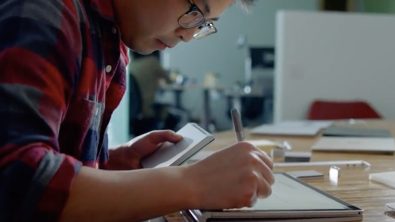 Man using pen on Surface Book in clipboard mode.