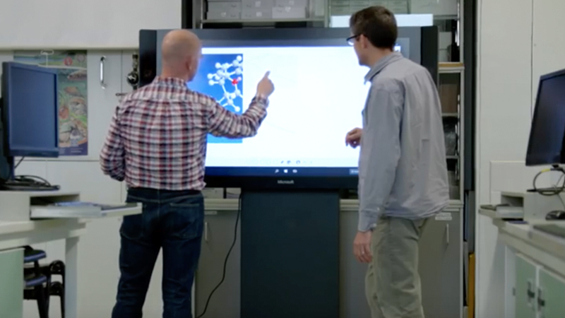 Two men use touchscreen onSurfaceHub