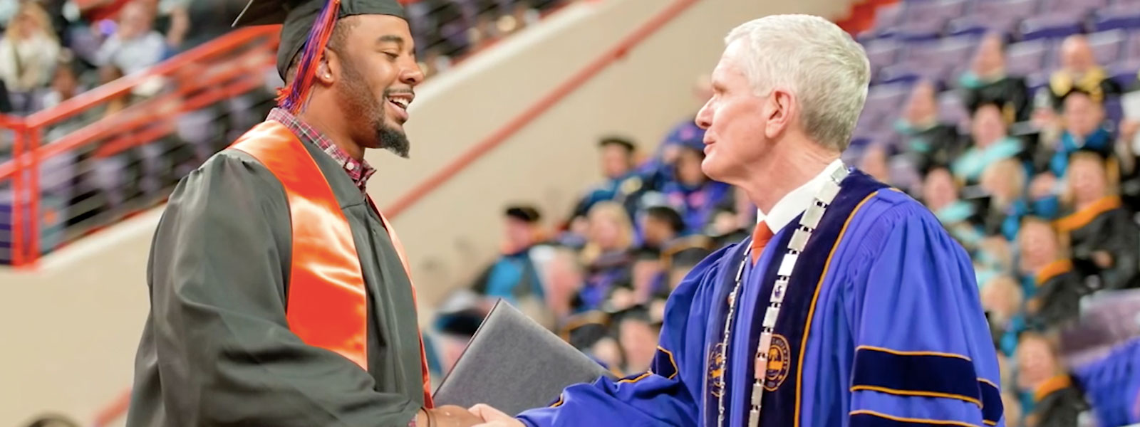 Faculty member hands student a diploma at graduation at Clemson University.