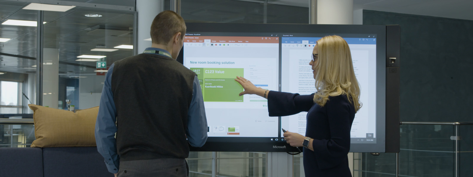 A man and woman stand in front of a Surface Hub with PowerPoint and Word open on the screen.