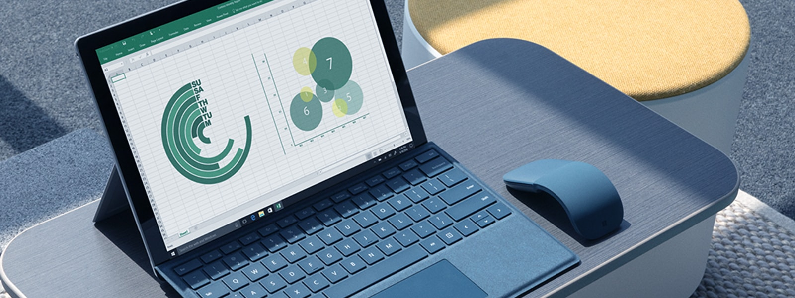 Surface Pro with LTE Advanced with Excel on the screen and Surface ArcTouch Mouse sit on a table in a Steelcase space.
