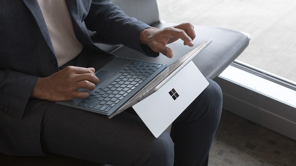 Man uses Cobalt Surface Pro on his lap while he sits at an airport.