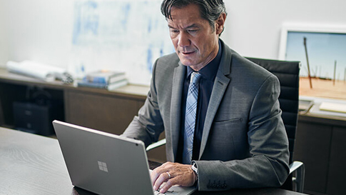 Man types on Surface Book at a desk.