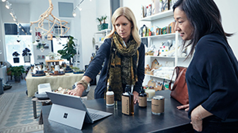 Two women look at a Surface Pro 4.