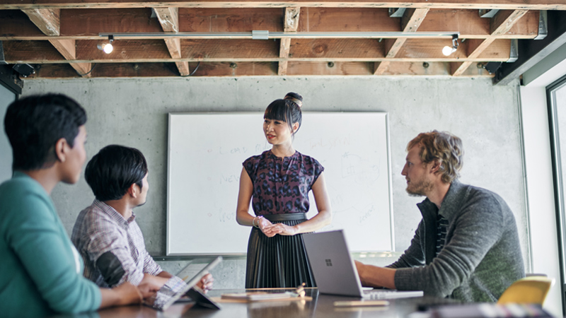 Woman gives presentation in conference room.