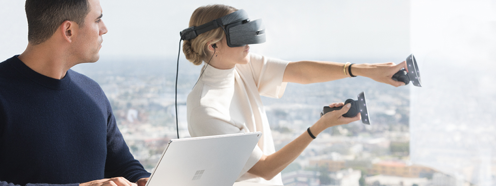 A man using a Surface Book 2 watching a woman  beside him using a Windows Mixed Reality headset and motion controllers that is paired with his Surface Book 2